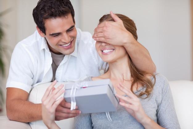 Homme couvrant les yeux de sa petite amie tout en lui donnant un cadeau