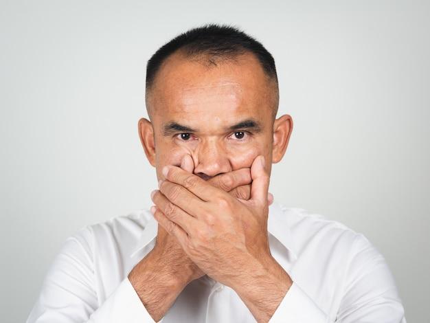 L'homme couvre la bouche avec la main pour le silence