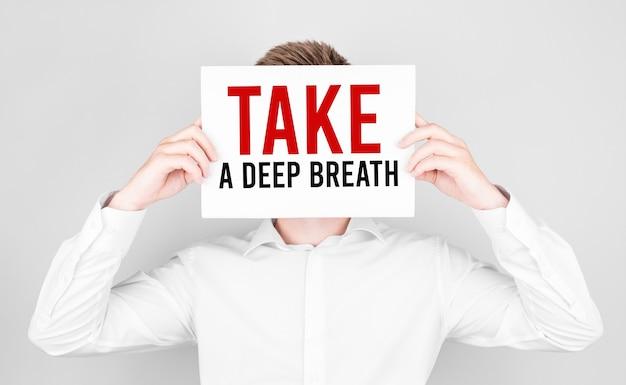 L'homme couvre son visage avec un papier blanc avec du texte prenez une profonde respiration