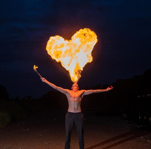Homme cracheur de feu soufflant une grande flamme en forme de coeur de sa bouche la nuit