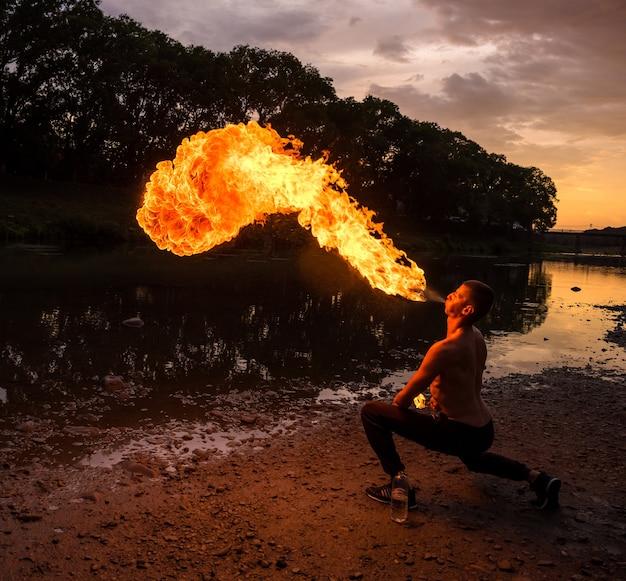 Homme cracheur de feu soufflant une grande flamme de sa bouche