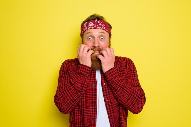L'homme craintif avec la barbe et le bandana dans la tête a peur de quelque chose