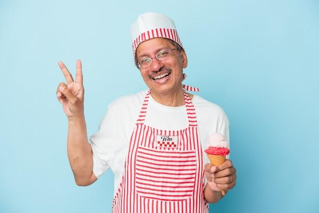 Homme de crème glacée américain senior tenant une glace isolée sur fond bleu joyeux et insouciant montrant un symbole de paix avec les doigts.