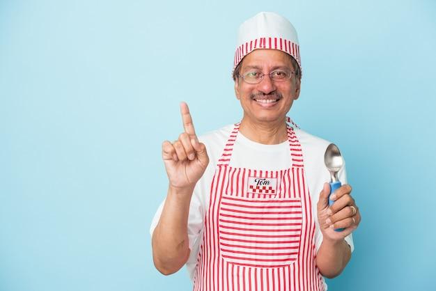 Homme de crème glacée indien senior tenant une boule isolée sur fond bleu montrant le numéro un avec le doigt.