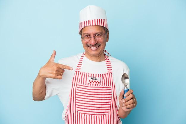Homme de crème glacée indien senior tenant une boule isolée sur fond bleu personne pointant à la main vers un espace de copie de chemise, fier et confiant