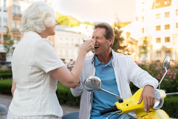 Homme avec de la crème glacée en riant.