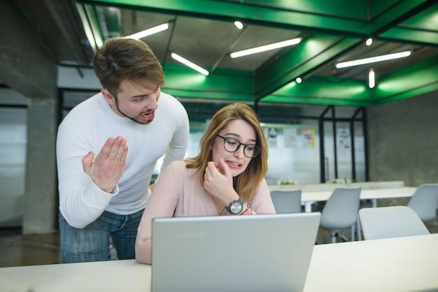 Un homme crie à une belle fille assise à la table et travaillant à l'ordinateur.