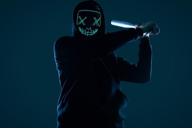 Homme criminel anonyme avec batte de baseball dans un sweat à capuche noir et un masque de néon