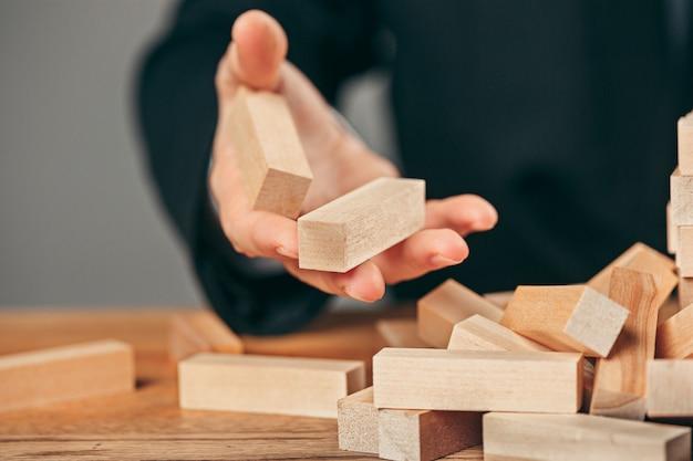 Homme et cubes en bois sur table. concept de gestion