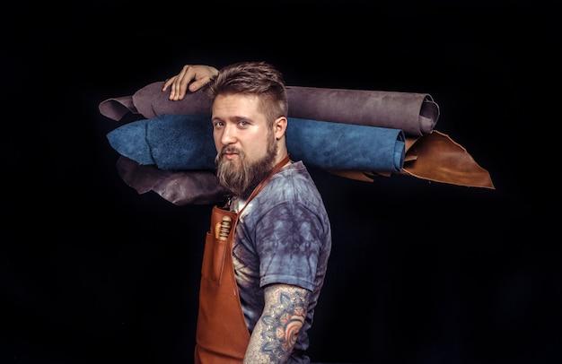 Homme en cuir découpant des articles en cuir au bureau