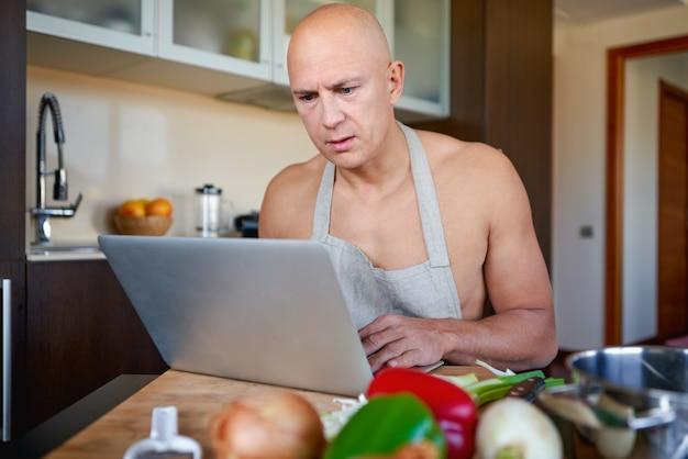 Homme cuisinant avec l'aide de recette sur tablette