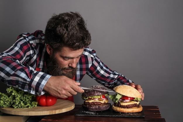 Homme cuisinant un hamburger noir frais fait maison close up