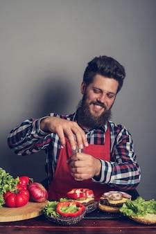 Homme cuisinant des hamburgers frais faits maison se bouchent