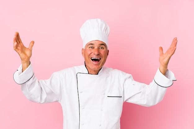 Homme cuisinier d'âge moyen isolé recevant une agréable surprise, excité et levant les mains.