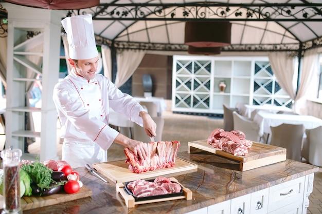 Un homme cuisinier coupe la viande avec un couteau dans un restaurant.