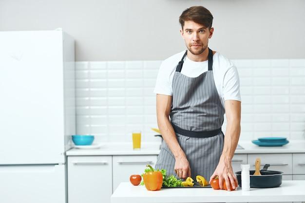 Homme cuisinier cuisine dans la cuisine, des aliments sains faits maison
