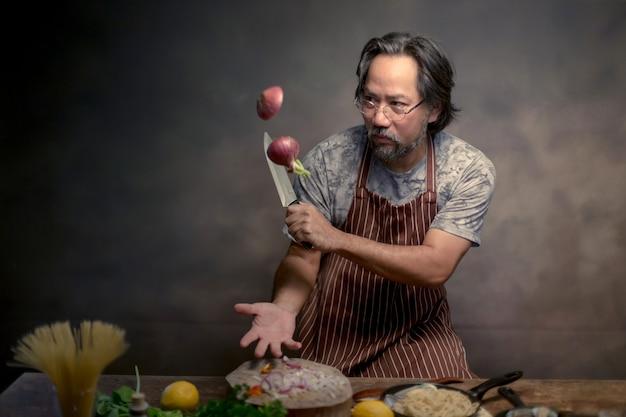 Homme cuisinier hipster chef avec beau barbu avec un couteau.