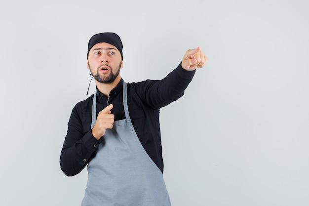 Homme cuisinier pointant vers l'extérieur en chemise, tablier et regardant concentré. vue de face.