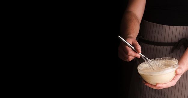 Homme cuisinier tenant un bol avec et fouettant le mélange