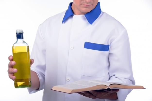 Homme cuisinier tenant le livre de recettes et une bouteille d'huile.