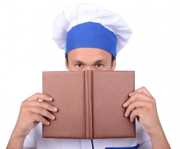 Homme cuisinier tenant livre de recettes pensant quoi faire cuire.