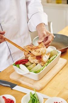 Homme, cuisson du poulet avec des légumes