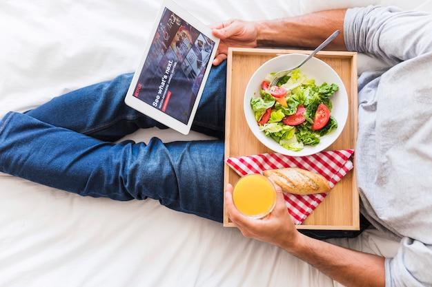 Homme de culture avec des aliments sains parcourant le site netflix