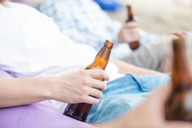 Homme de culture avec de la bière au repos entre amis