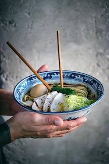 Homme de culture avec bol de délicieux ramen et baguettes