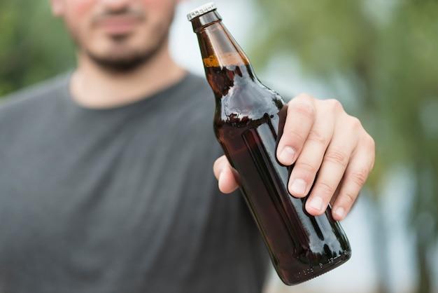Homme de culture montrant une bouteille de bière dans le parc