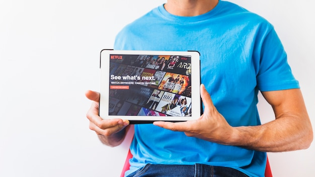 Homme de culture montrant une tablette avec la page de démarrage de netflix