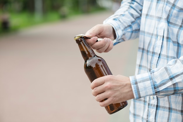 Homme de culture ouvrant la bière au bar