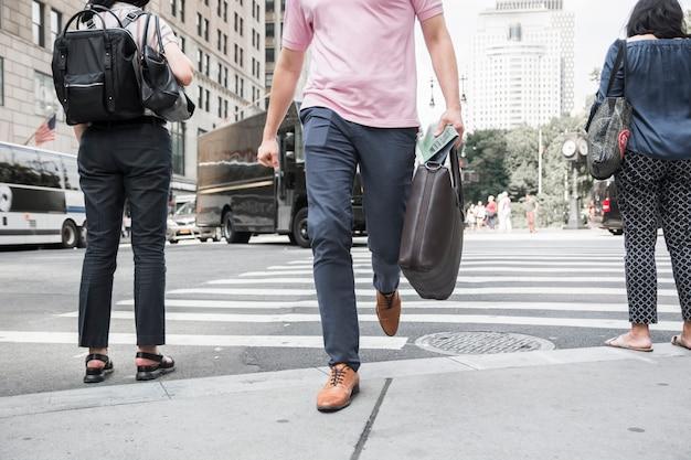 Homme de culture avec sac traversant la route