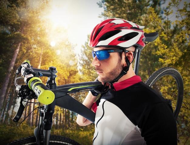 L'homme cycliste détient épaulé son vélo de montagne