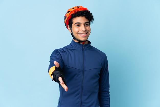 Homme cycliste vénézuélien sur bleu se serrant la main pour conclure une bonne affaire