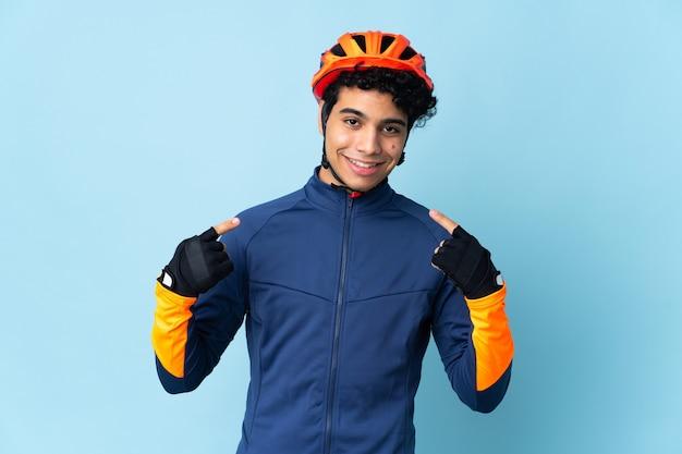 Homme cycliste vénézuélien isolé sur fond bleu donnant un geste de pouce en l'air