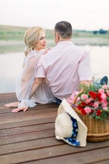 Homme et dame, assis ensemble sur le pont de bois au bord du lac