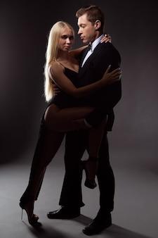Un homme dans un accès de passion déboutonne la robe d'une jeune femme bien-aimée