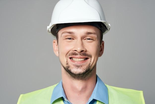 Homme dans l'arrière-plan clair de travail professionnel uniforme de construction