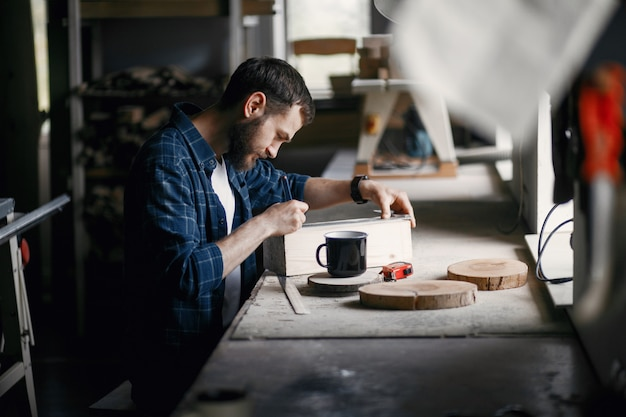 Homme dans l'atelier avec un bois