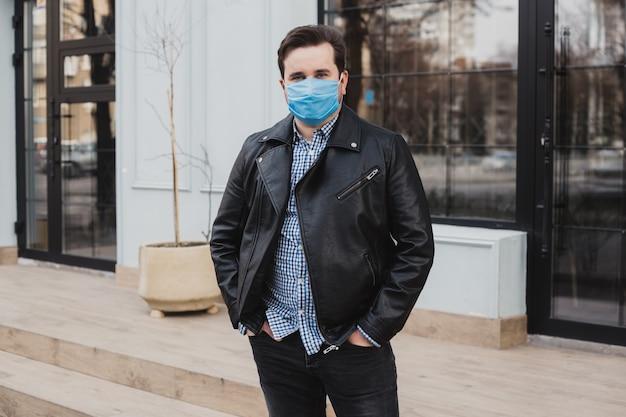 Homme dans un bandage chirurgical sur fond d'un immeuble moderne, coronavirus, maladie, infection, quarantaine, masque médical