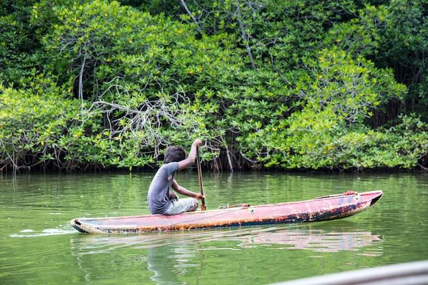 Homme dans le bateau flottant sur la rivière dans la jungle tropicale, ceylan. paysage du sri lanka