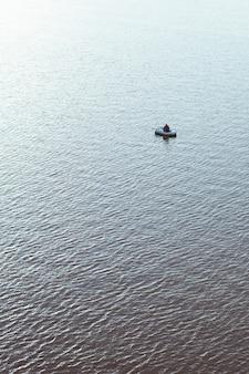 Homme dans un bateau pneumatique avec une canne à pêche dans la mer