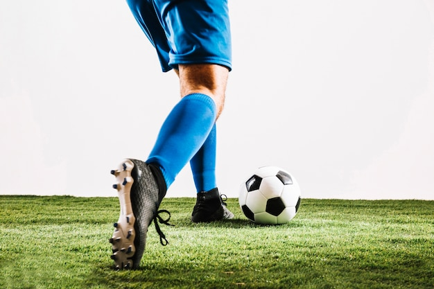 Homme dans les bottes de football bottant le ballon