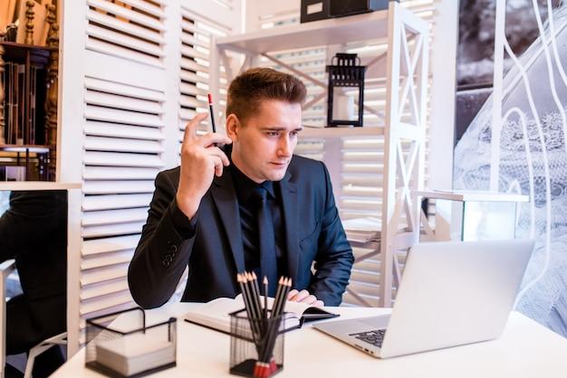 Un homme dans le bureau mord un crayon
