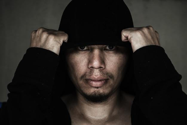 Homme dans le capot avec le visage effrayant dans le noir