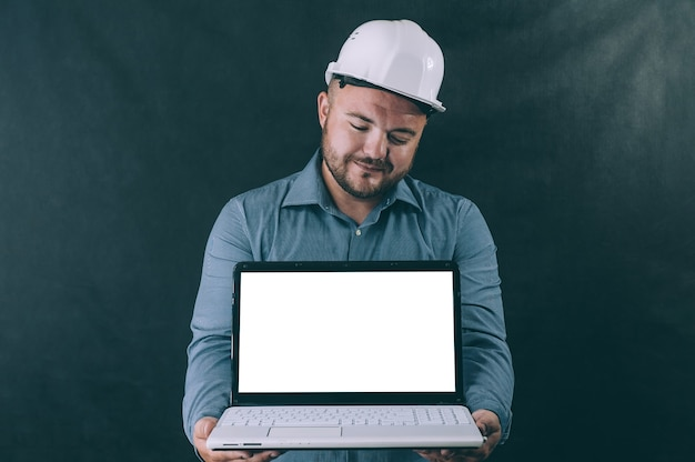Un homme dans un casque de construction avec un ordinateur portable dans ses mains