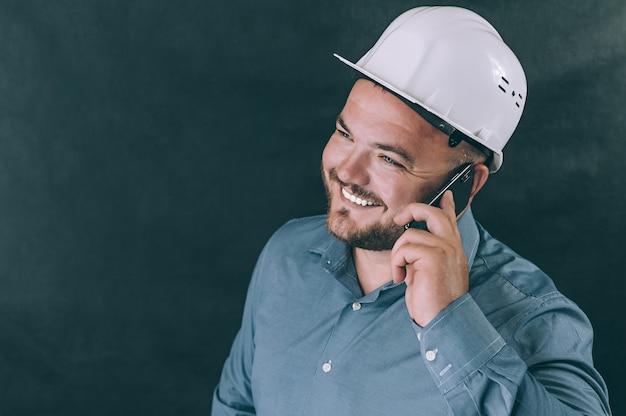 Un homme dans un casque de construction parlant au téléphone
