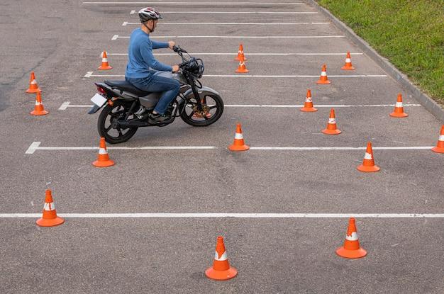 Homme, dans, casque, sur, motocyclette, pratiquer, sur, parking, parmi, orange, trafic, cônes