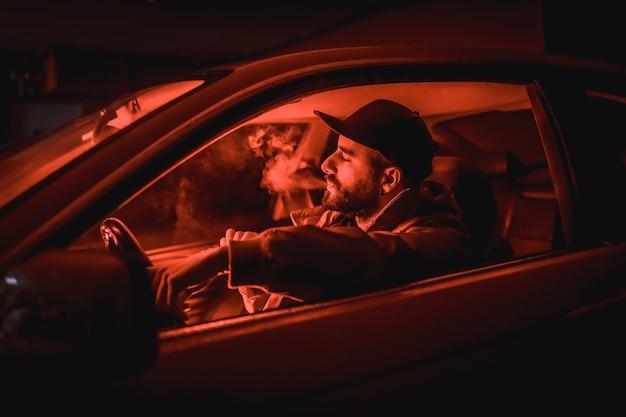 Homme dans une casquette conduisant une voiture fumant la nuit dans un garage éclairé par un feu rouge, voiture de sport